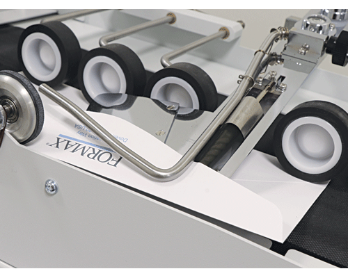 Precision moistening roller and flap feeding plate accurately seal both stacked and nested envelopes